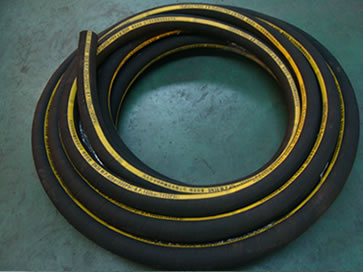 A roll of black gunite hose is on the floor of the workshop.