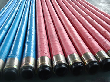 Many steel wire reinforced concrete pump hose assemblies are on the floor of the workshop.