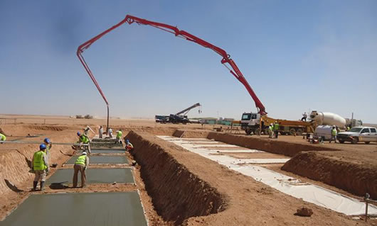 A large equipment is pouring concrete to the ground with concrete pump hose.