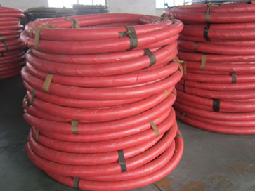 Several rolls of concrete pump hoses are on the floor of the warehouse.