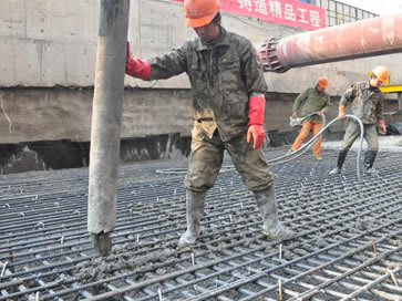Several workers are pouring concrete to the bridge which is under construction with steel wire reinforced concrete pump hoses.