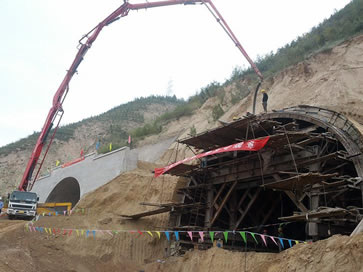 A person is pouring concrete to the tunnel which is under construction with steel wire reinforced concrete pump hoses.