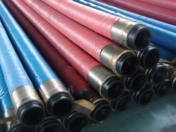 Many fabric reinforced concrete pump hose assemblies are on the floor of the workshop.