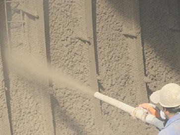 A worker is spraying the mixture of dry sand, cement and water to the ground with the gunite hose.