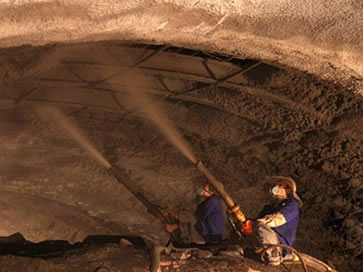 The robotic equipment is spraying the mixture of dry sand, cement and water to the surface of the underground mining with gunite hose.